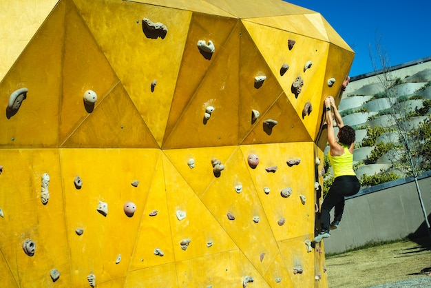 Brave woman training her climbing muscles on a climbing wall in the sun.