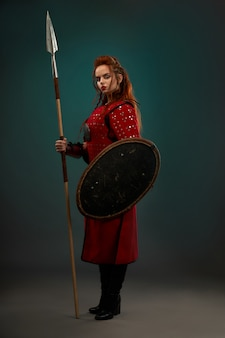 Brave woman warrior with weapon posing in studio.