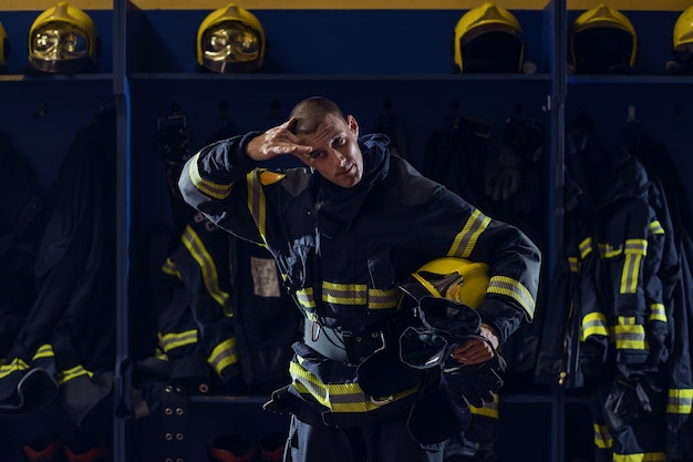 Brave young attractive fireman in protective uniform, with helmet under armpit wiping sweat from forehead and resting after action while standing in fire station.