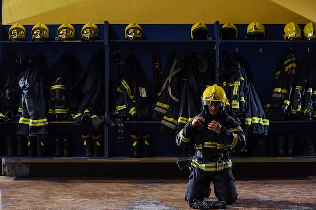 Brave young firefighter in protective uniform kneeling and putting on helmet on head.