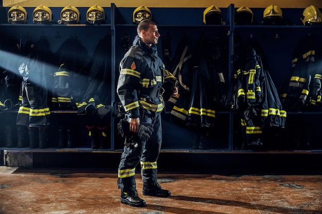 Brave young firefighter standing in fire station in protective uniform and holding helmet under armpit.