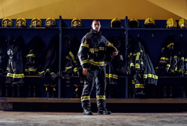 Brave young firefighter standing in fire station in protective uniform and holding helmet.