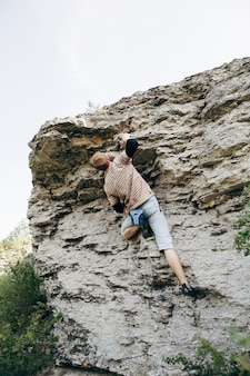 Brave young man climbs the cliff