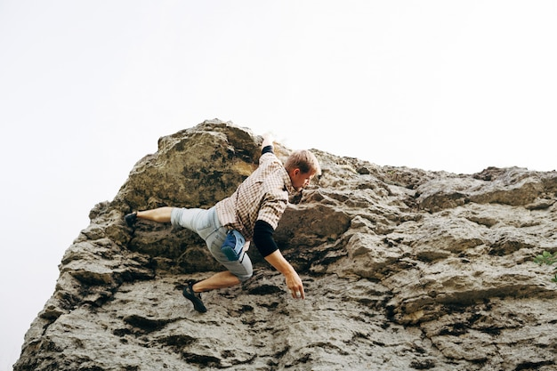 Brave young man climbs the top of the cliff