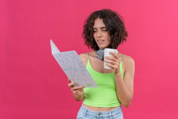 Una coraggiosa giovane donna graziosa con i capelli corti in top verde in cuffie che tiene una tazza di caffè di plastica guardando una mappa con sicurezza