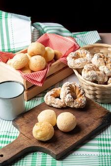 브라질 치즈 빵과 달콤한 비스킷, 녹색 체크 무늬 식탁보가 있는 탁자 위에 있는 커피 한 잔, 선별적인 집중.