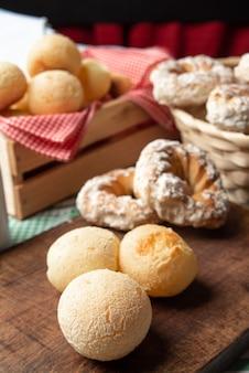 녹색 체크 무늬 식탁보가 있는 테이블에 브라질 치즈 빵과 달콤한 비스킷, 선택적 초점.