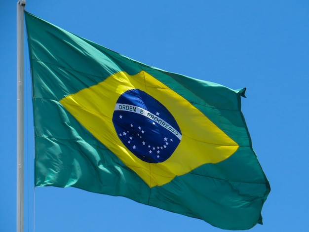 Флаг бразилии развевается на ветру в центре флага со словами порядок и прогресс