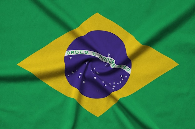 Brazil flag  is depicted on a sports cloth fabric with many folds.