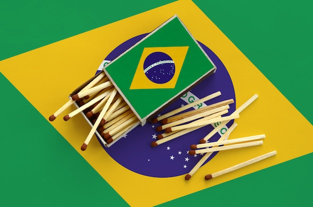 Brazil flag  is shown on an open matchbox, from which several matches fall and lies on a large flag