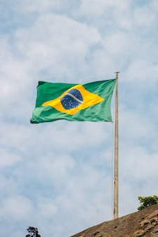 Brazil flag outdoors with a beautiful blue sky in rio de janeiro.