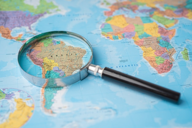 Brazil, magnifying glass close up with colorful world map