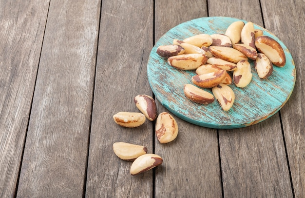 Brazil nuts on a board over wooden table with copy space.