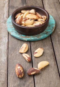 Brazil nuts on a board over wooden table.