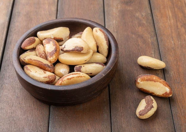 Brazil nuts on a bowl over wooden table.