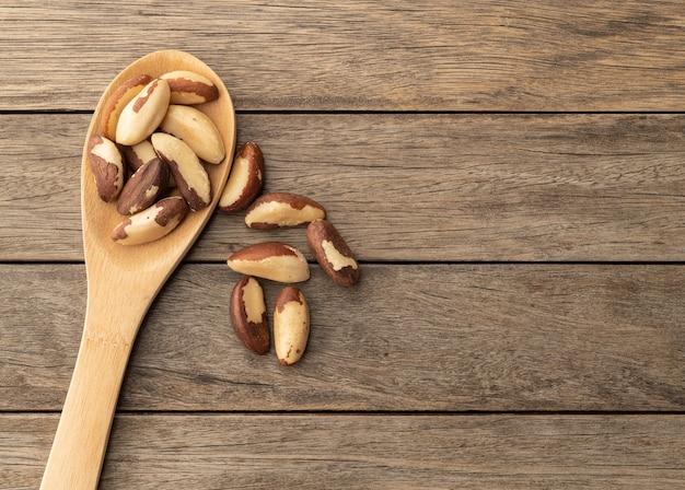 Бразильские орехи в ложке над деревянным столом с копией пространства.
