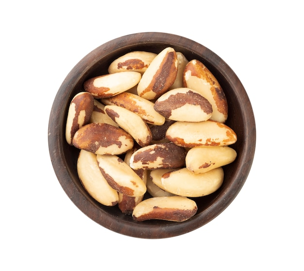 Brazil nuts on a plate isolated over white surface.