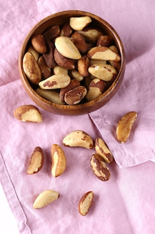 Brazil nuts in a wooden bowl on a pink linen napkin
