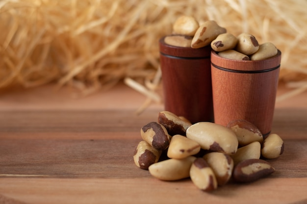 Brazil nuts on a wooden table and in a wooden cups with straw background. (castanha do brasil ou castanha do para)