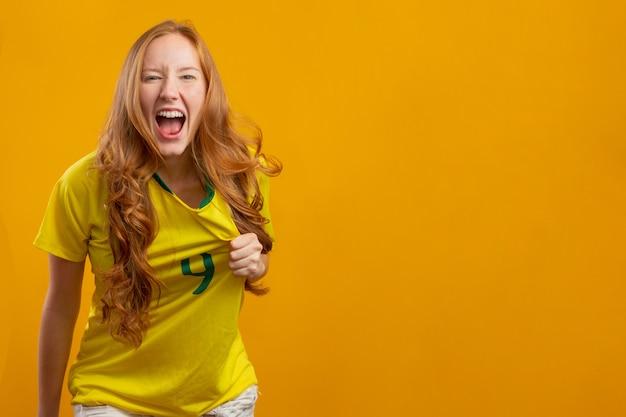 ブラジルの支持者。サッカーで祝うブラジルの赤毛の女性ファン、サッカーはブラジルの色と一致します。