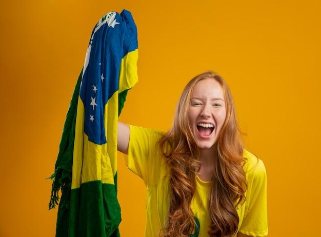 Brazil supporter. brazilian redhead woman fan celebrating on soccer, football match  brazil colors. wearing a t-shirt, flag and fan hat.