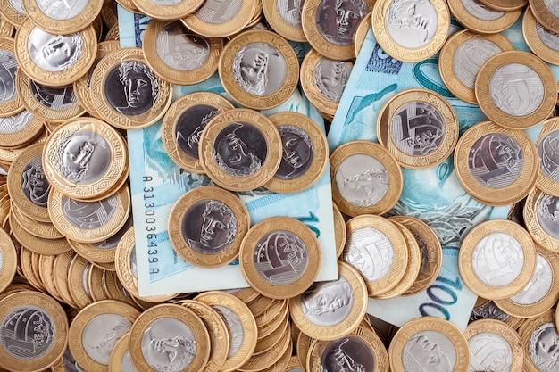 ブラジルの1リアルコインと100のレアル紙幣