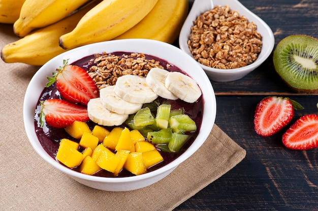 Brazilian açaí­ in a bowl accompanied by tropical fruits. fruit of the amazon