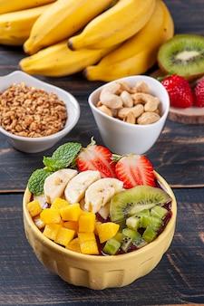 Бразильский асаи в миске в сопровождении тропических фруктов. плод амазонки