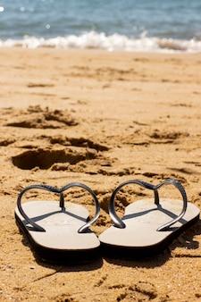 ブラジルのビーチコースト。砂と海の背景のスリッパ。