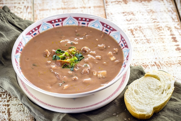 Brazilian bean broth or soup with vegetables and meat, called bean broth, slice of bread on the side