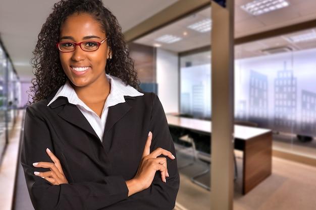 흐리게 사무실 공간에 카메라를보고 브라질 흑인 비즈니스 여자. 공간을 복사하십시오.