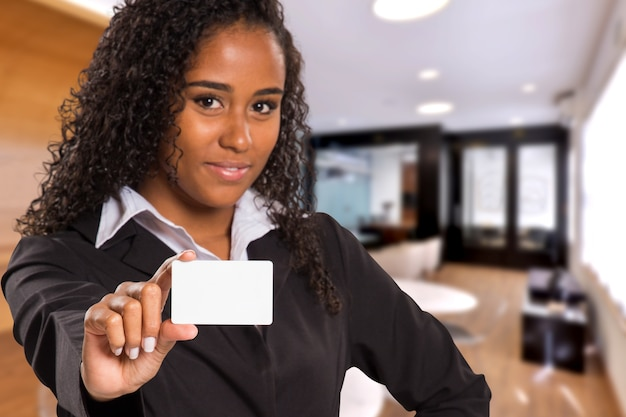 Brazilian black business woman with white card in the hand looking at camera on blurred office space. copy space.