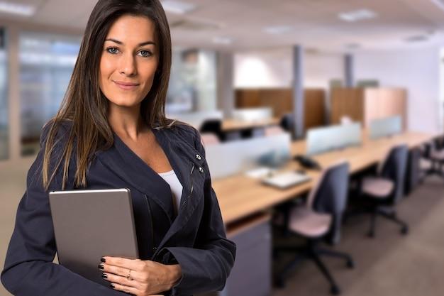 흐릿한 사무실 공간에서 카메라를보고 태블릿 브라질 비즈니스 여자. 공간을 복사하십시오.