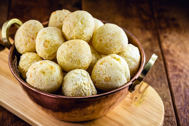 미나스 제 라이스주의 전형적인 음식 인 브라질 치즈 빵을 오래된 구리 냄비에 담았습니다.