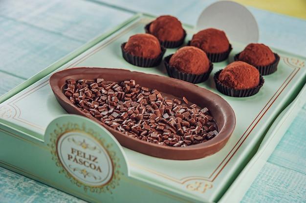 Бразильское шоколадное пасхальное яйцо в подарочной коробке с надписью happy easter с бразильскими шоколадными конфетами trufas - ovo de chocolate de colher