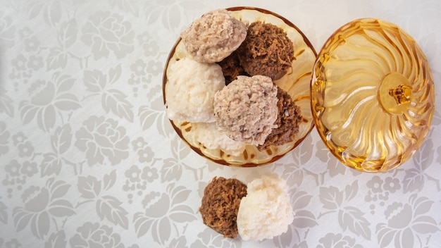 白いタオルでテーブルの上のガラスの瓶に入れられたブラジルのコカダ(ココナッツキャンディー)、選択的な焦点。
