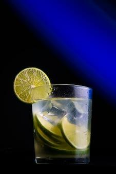 Caipirinha라는 브라질 칵테일. 푸른 빛이 있는 어두운 배경에 레몬, 얼음, cachaã§a. 복사 공간