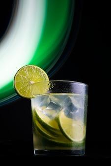 Caipirinha라는 브라질 칵테일. 어두운 배경에 레몬, 얼음, 카샤가 있는 조명. 복사 공간