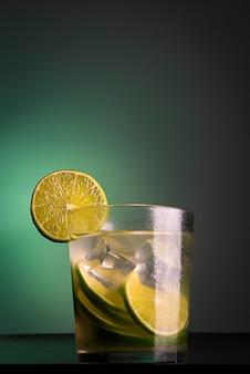 Caipirinha라는 브라질 칵테일. 녹색 불빛과 함께 어두운 배경에 레몬, 얼음, cachaã§a. 복사 공간