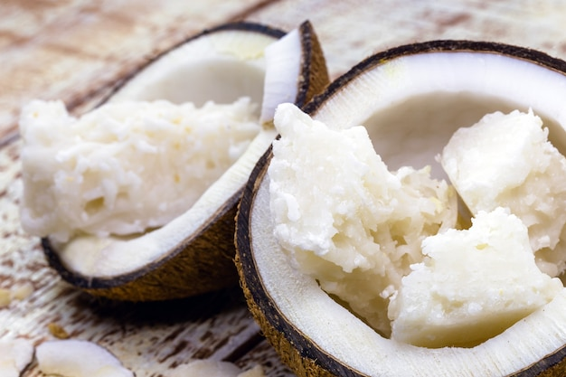 白い木製の背景に、2つの開いたココナッツの中に「コカダ」と呼ばれるブラジルのココナッツキャンディー