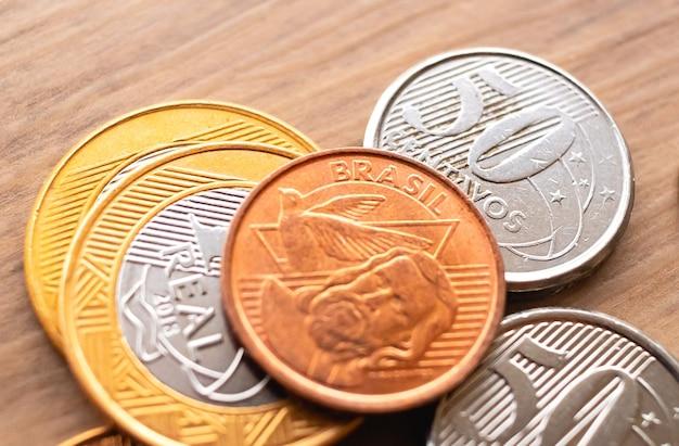 금융 및 저축 개념을 위한 매크로 사진의 나무 표면에 있는 브라질 동전