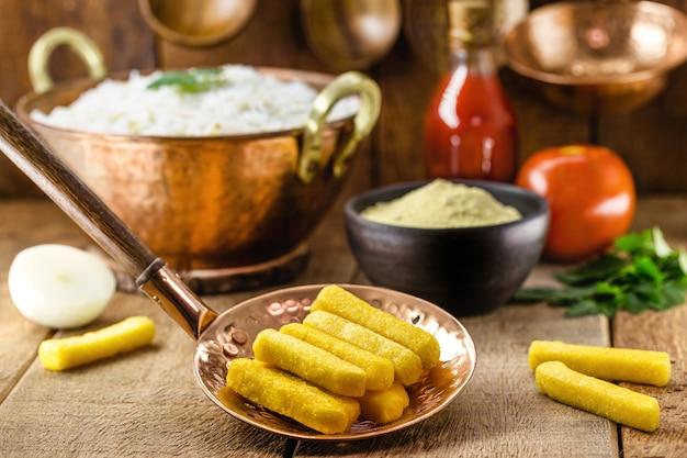 Бразильская кухня, называемая полента, традиционный бразильский картофель фри с кукурузной мукой и соусом на поверхности, деревенская обстановка.