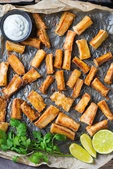 Еда бразильской кухни, латинские закуски. жареные юкка, юка, маниока, палочки из маниоки с соусом из кинзы. плоский фон вид сверху
