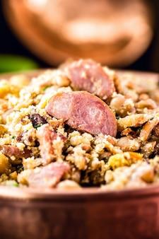 Бразильское кулинарное блюдо, фасоль со свининой, пепперони, фарофа и овощи.