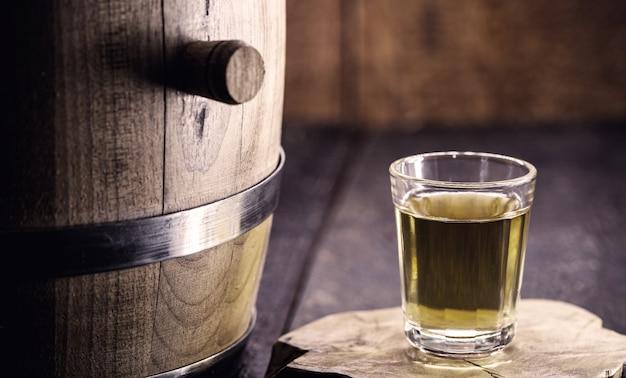 素朴な木製の背景を持つ「pinga」または「cachaã§a」と呼ばれるブラジルの蒸留飲料