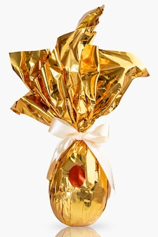 Brazilian easter egg, wrapped in golden yellow paper, on white surface.