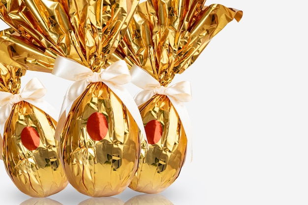 Бразильское пасхальное яйцо, завернутое в золотисто-желтую бумагу, на белой поверхности.
