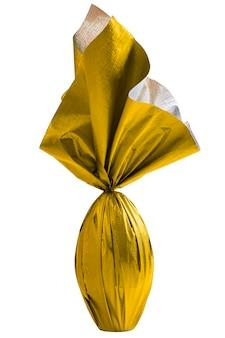 Uovo di pasqua brasiliano avvolto in carta gialla su un muro bianco