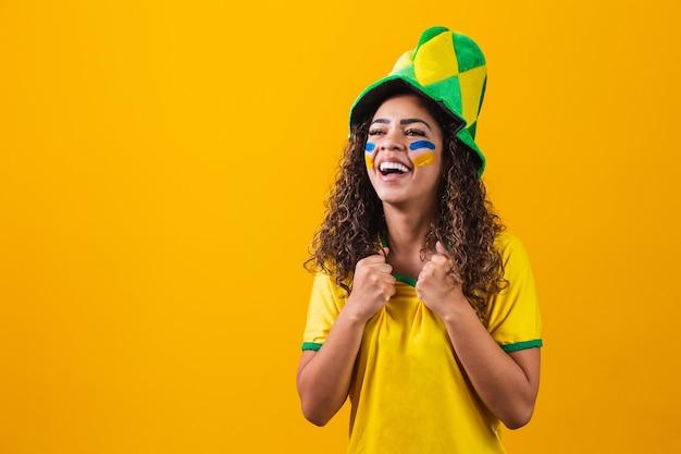 브라질 팬. 노란색 배경에서 축구나 축구 경기를 축하하는 브라질 팬. 브라질의 색상입니다.