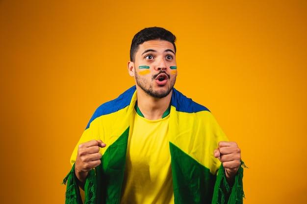 黄色の背景に群衆の中で応援しているブラジルのファン。
